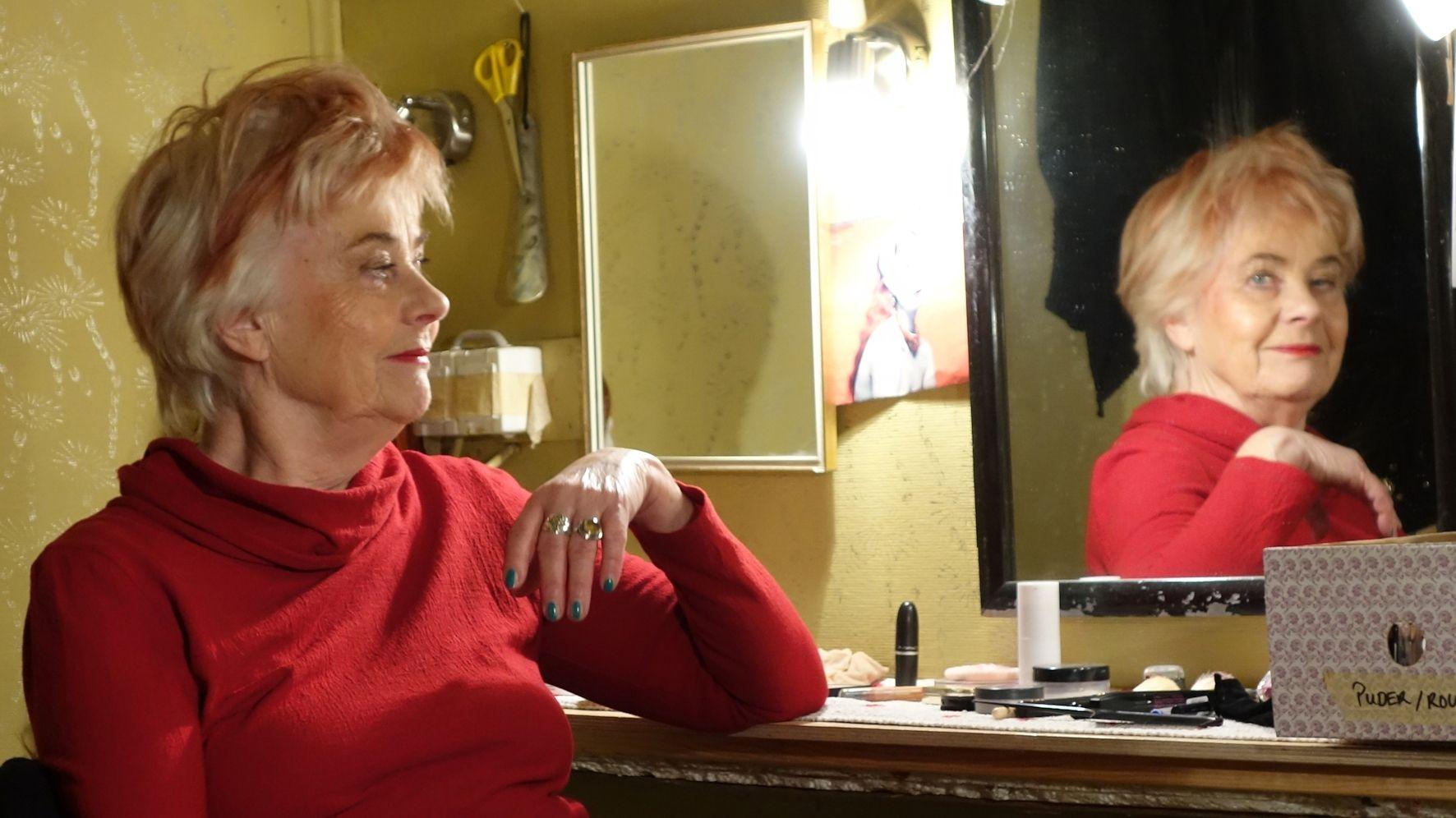 Schauspielerin und TamS-Leiterin Anette Spola sitzt in ihrer Umkleide vor dem Schminktisch, in dem sie sich spiegelt