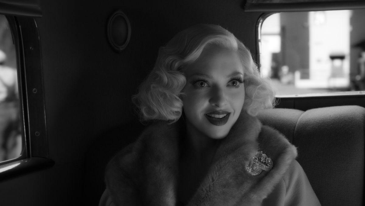 Eine blonde Frau in den 1930er-Jahren mit schulterlangem Haar sitzt in einer alten Limousine
