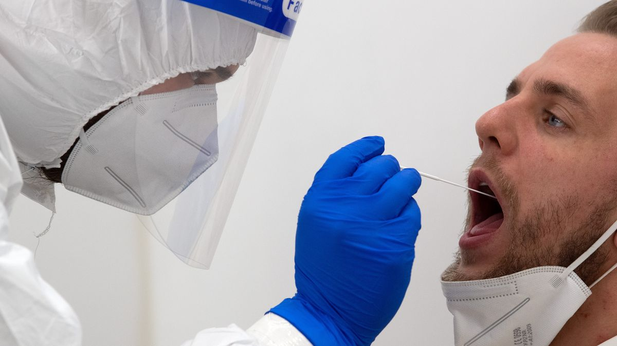Mann in Schutzanzug nimmt Rachenprobe bei Patient