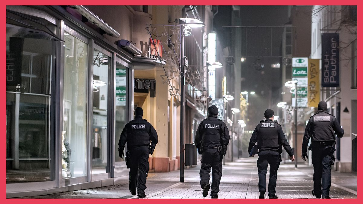 Vier Polizisten gehen durch eine leere Einkaufspassage bei Nacht auf Streife.