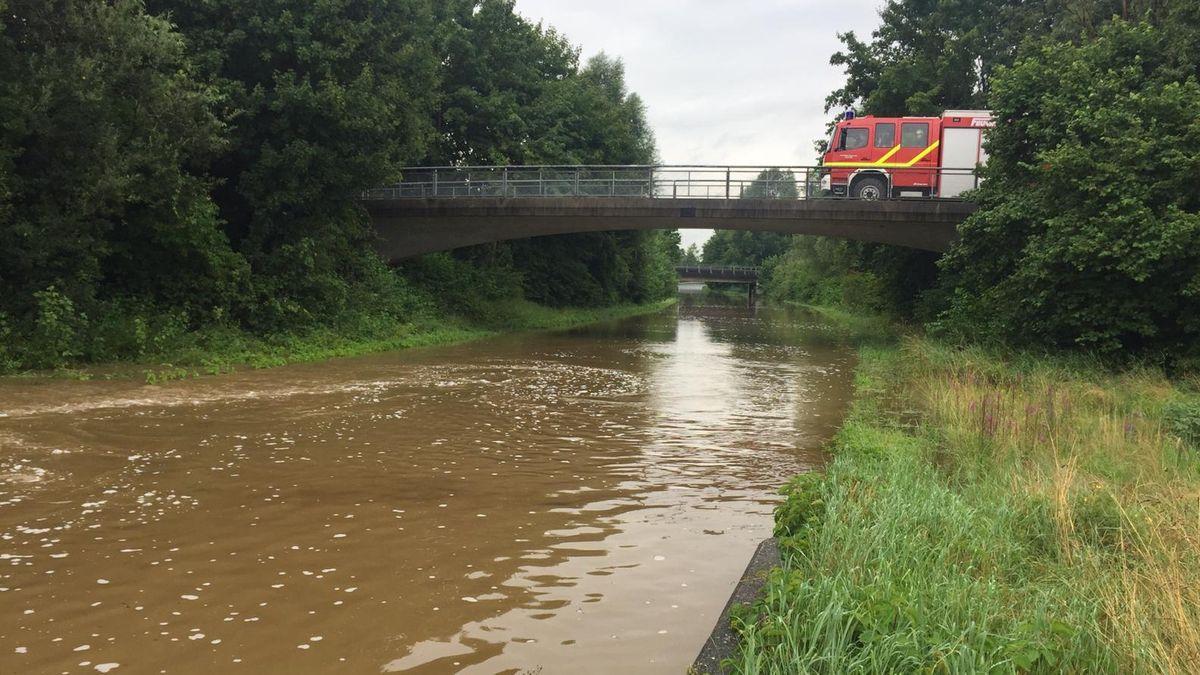 Die B15 bei Schechen ist so überflutet, dass es aussieht, als fließe dort ein Kanal. Auf einer Brücke steht ein Feuerwehrauto.