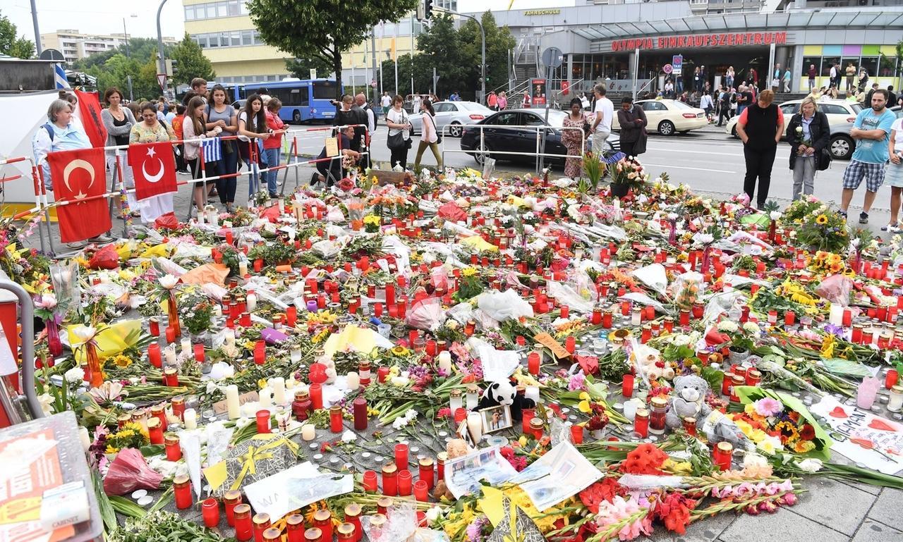ARCHIV - 25.07.2016, Bayern, München: Blumen und Kerzen liegen auf dem Gehweg vor dem Olympia-Einkaufszentrums (OEZ) in München (Bayern). Dort hatte am 22. Juli 2016 ein 18-jähriger neun Menschen erschossen. 2018 wurde die Tat als rassistischer Anschlag bewertet. (zu dpa «OEZ-Anschlag von München:Als der Hass neun Menschen tötete») Foto: picture alliance / dpa +++ dpa-Bildfunk +++