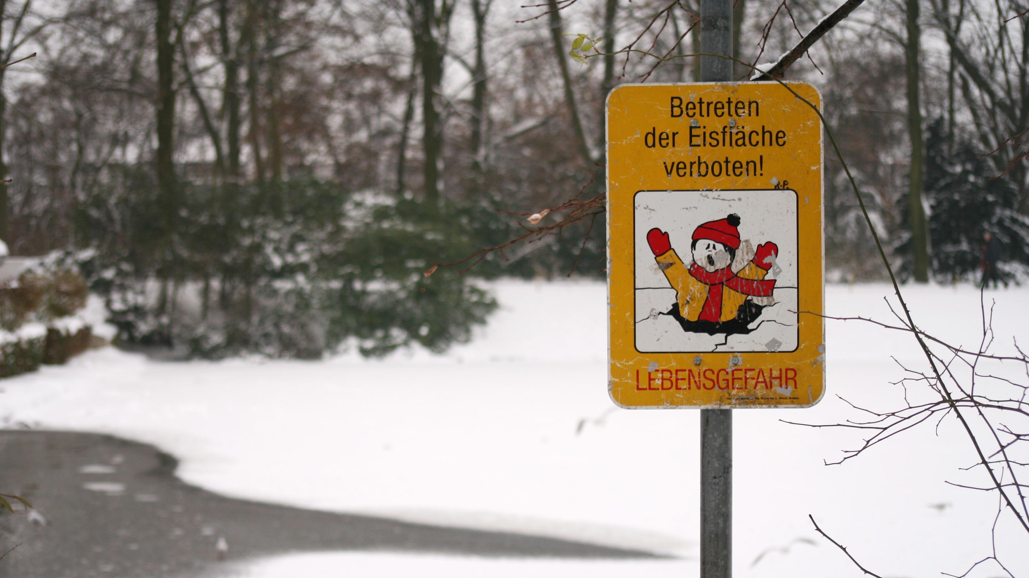 Ein Schild warnt an einem kleinen See vor dem Betreten der Eisfläche.