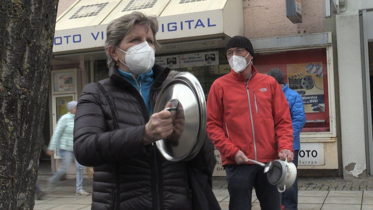 Eine Frau schlägt zwei Topfdeckel bei der Protestaktion des Wirtschaftsforums Freilassing