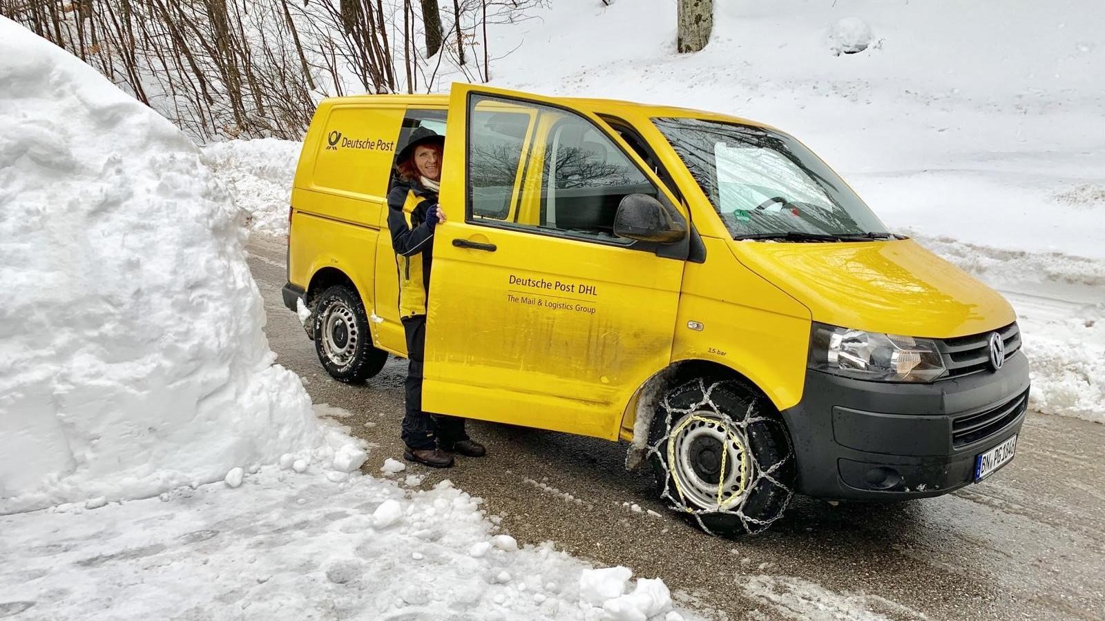 Postbotin Claudia steht im verschneiten Aschau neben ihrem gelben Postauto.
