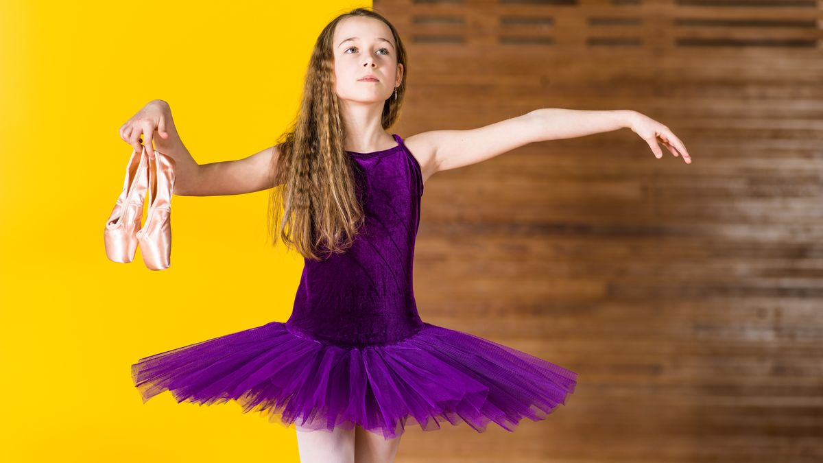 Ein Mädchen in lila Tanzkleid mit Ballettschuhen in der Hand vor einer gelb-braunen Wand