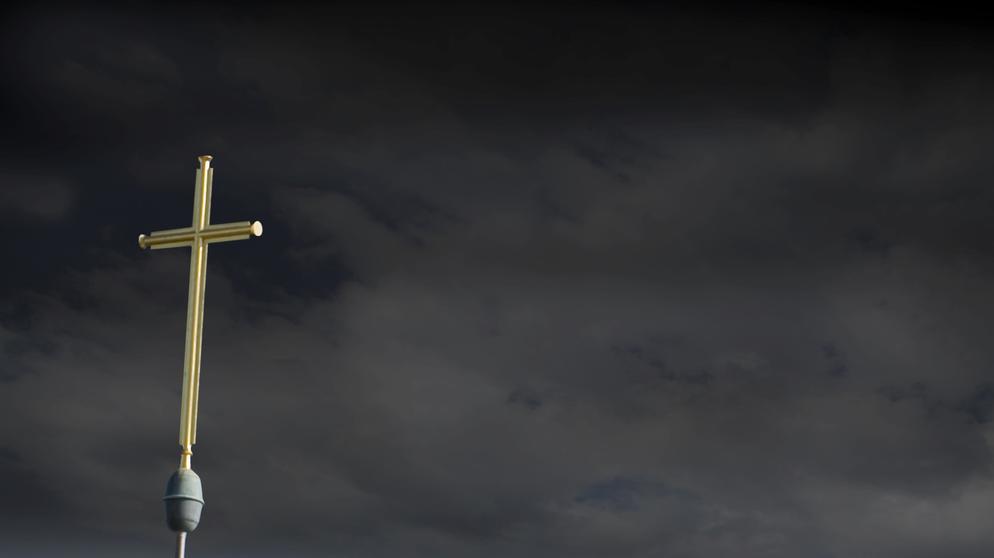 Ein goldenes Kreuz vor dunklem Himmel | Bild:dpa/ Martin Moxter
