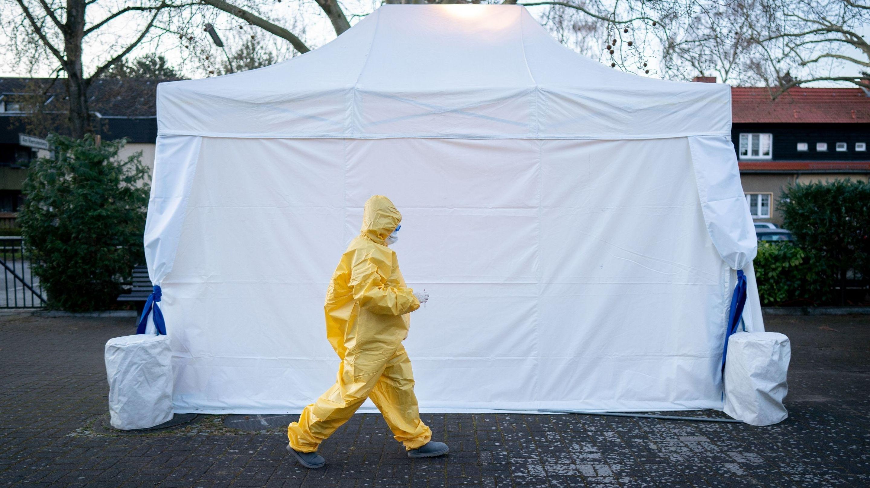 Eine Frau geht in einem Schutzanzug  in ein Zelt, in dem Rachenabstriche für den Test auf das Coronavirus durchgeführt werden (Symbolbild)