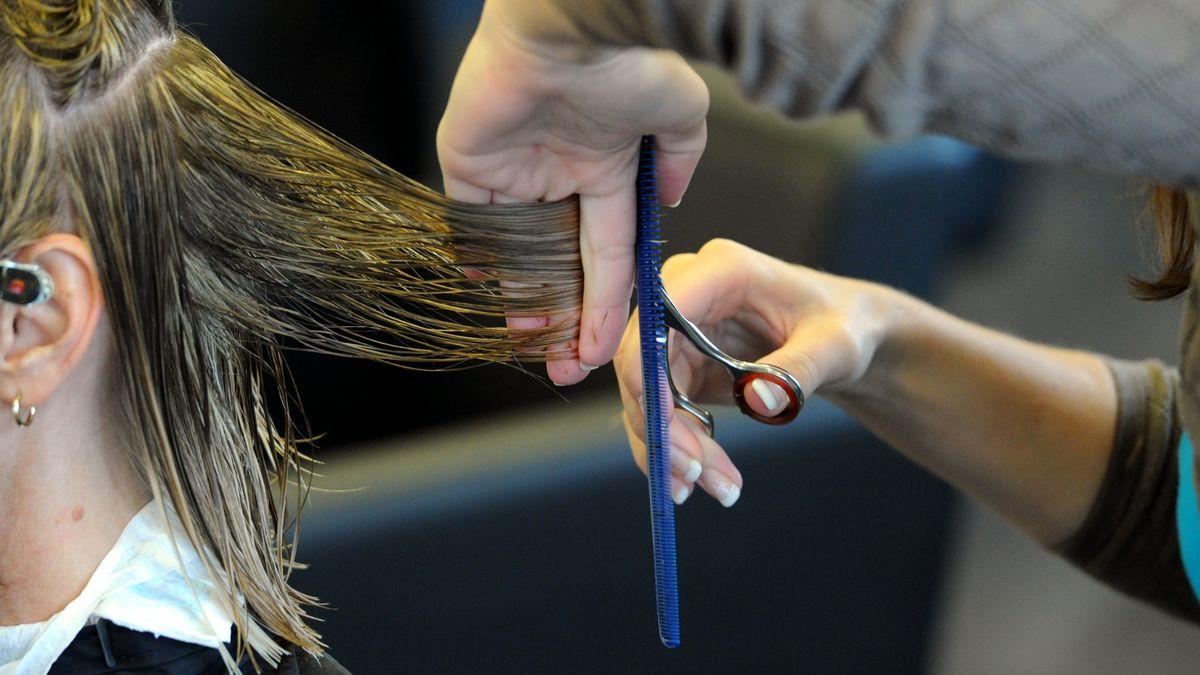 Eine Person schneidet einer anderen die Haare.