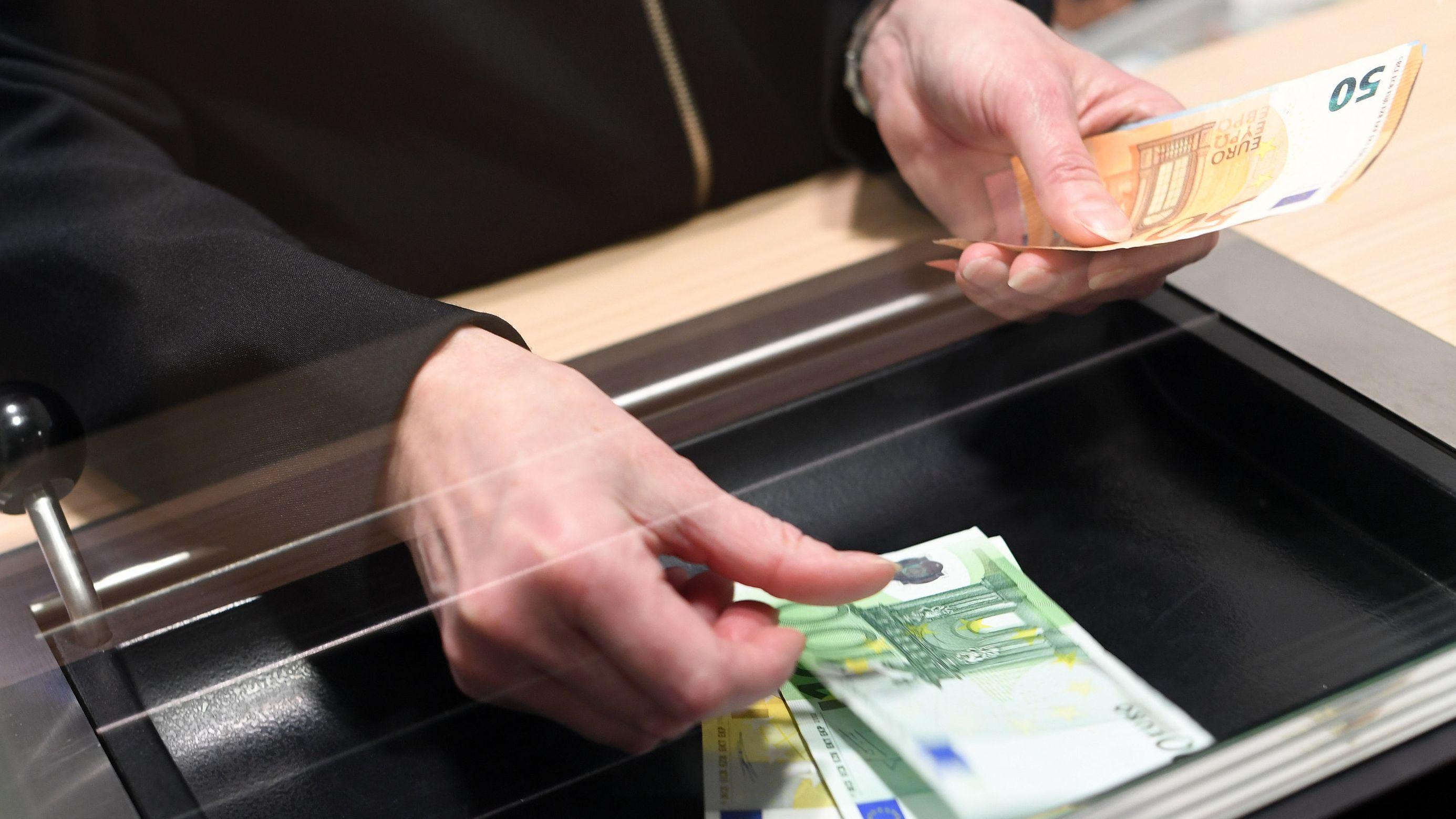 Am Bankschalter lässt sich sich eine Kundin oder ein Kunde Bargeld auszahlen.