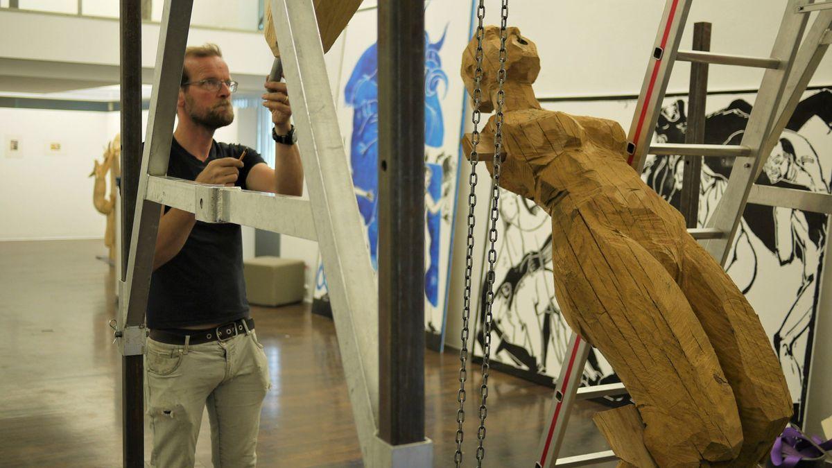 Der Künstler zieht eine Holzskulptur in Position
