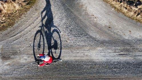 Luftaufnahme mit einer Drohne von einer Fahrradfahrerin auf einer Straße mit Schatten.