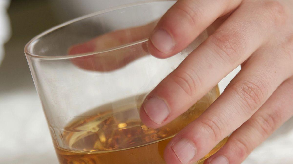 Symbolbild Schnapsglas und eine Hand