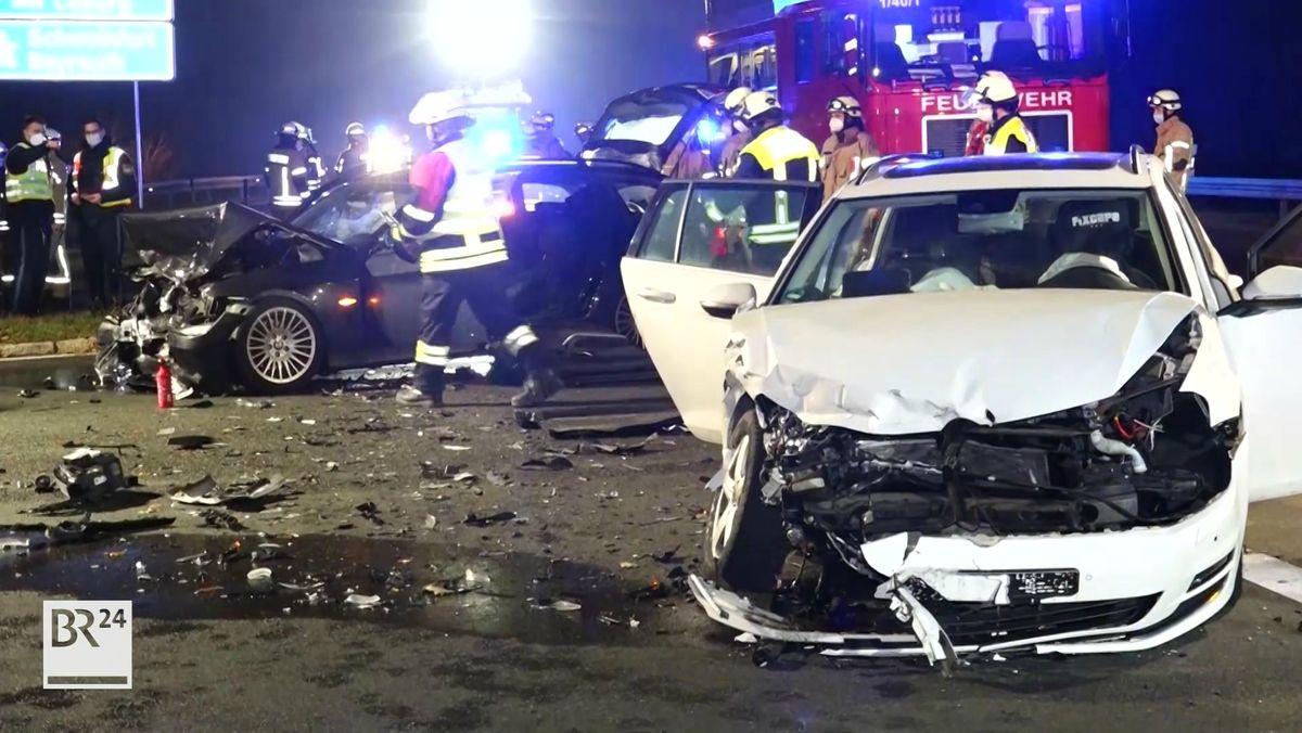 Zwei Unfallfahrzeuge stehen auf der Straße, im Hintergrund die Einsatzkräfte