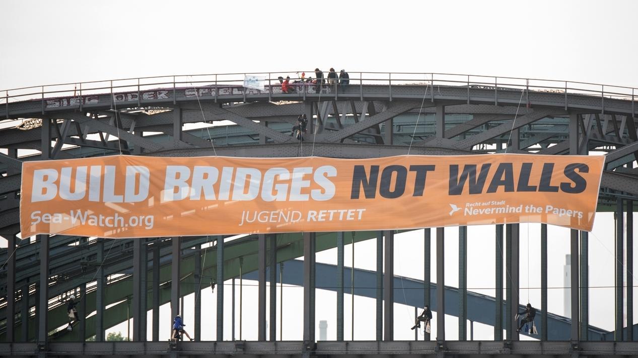 """Aktivisten verschiedener Organsiationen halten ein Transparent mit der Aufschrift """"Build bridges not walls"""" (Baut Brücken, keine Mauern)"""