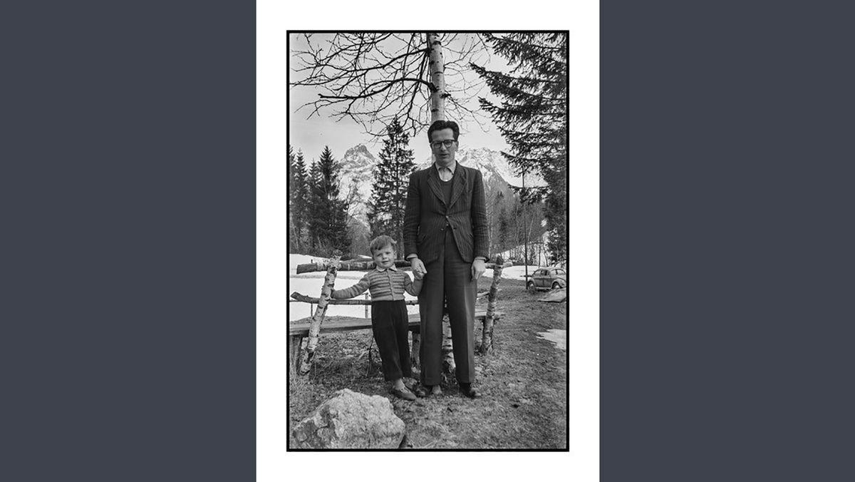 Schwarzweißfoto eines Mannes in Anzug und einem kleinen Jungen an der Hand