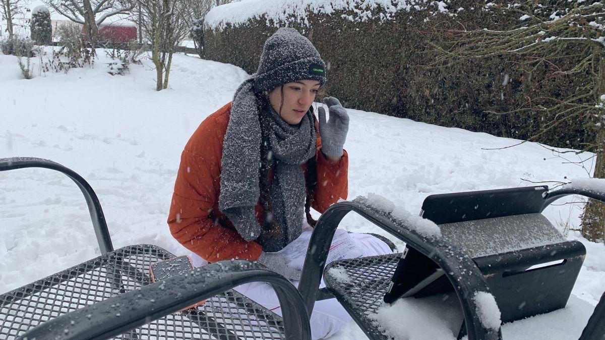 Selina Seebauer hockt mit Winterjacke, Schal, Handschuhen und Mütze in ihrem verschneiten Garten in Vierkirchen im Schneegestöber. Vor ihr auf einem Gartenstuhl steht ihr Laptop, daneben liegt das Smartphone.