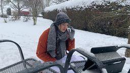 Selina Seebauer hockt mit Winterjacke, Schal, Handschuhen und Mütze in ihrem verschneiten Garten in Vierkirchen im Schneegestöber. Vor ihr auf einem Gartenstuhl steht ihr Laptop, daneben liegt das Smartphone. | Bild:privat