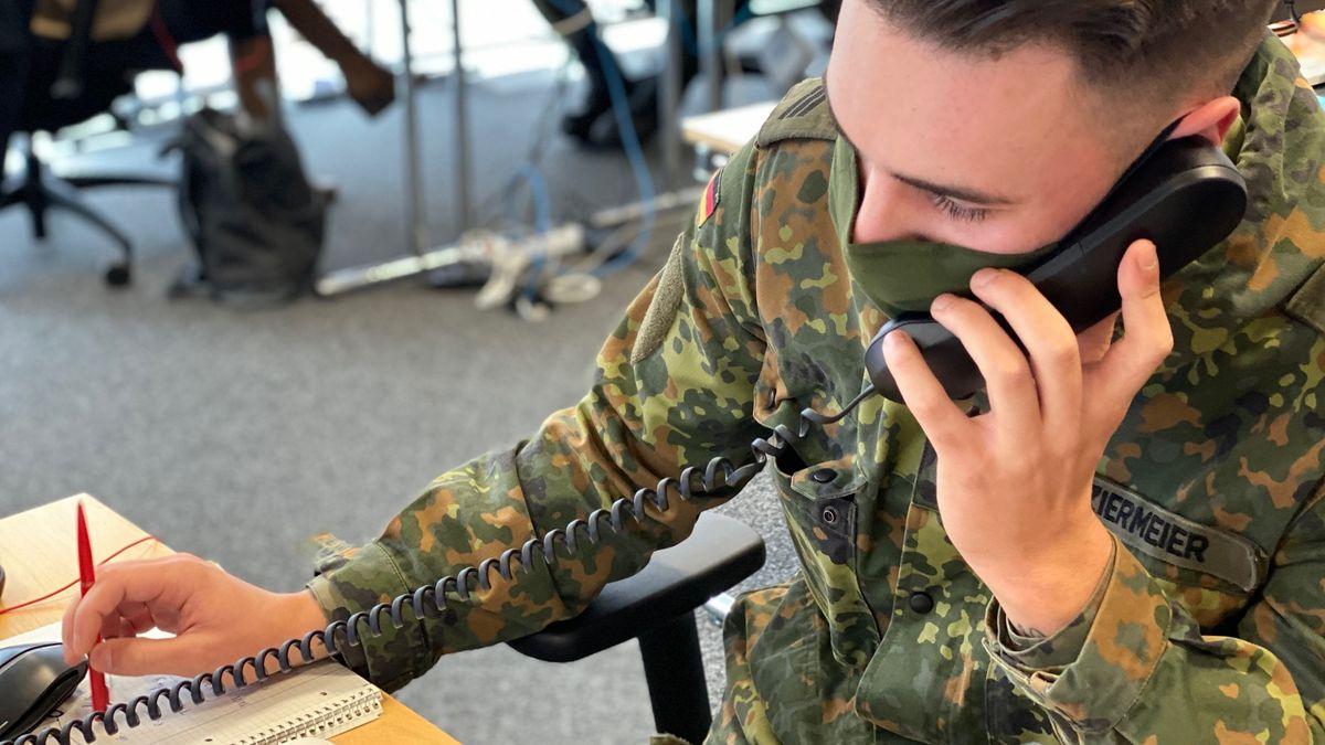 Soldat in Uniform mit Telefonhörer in der Hand