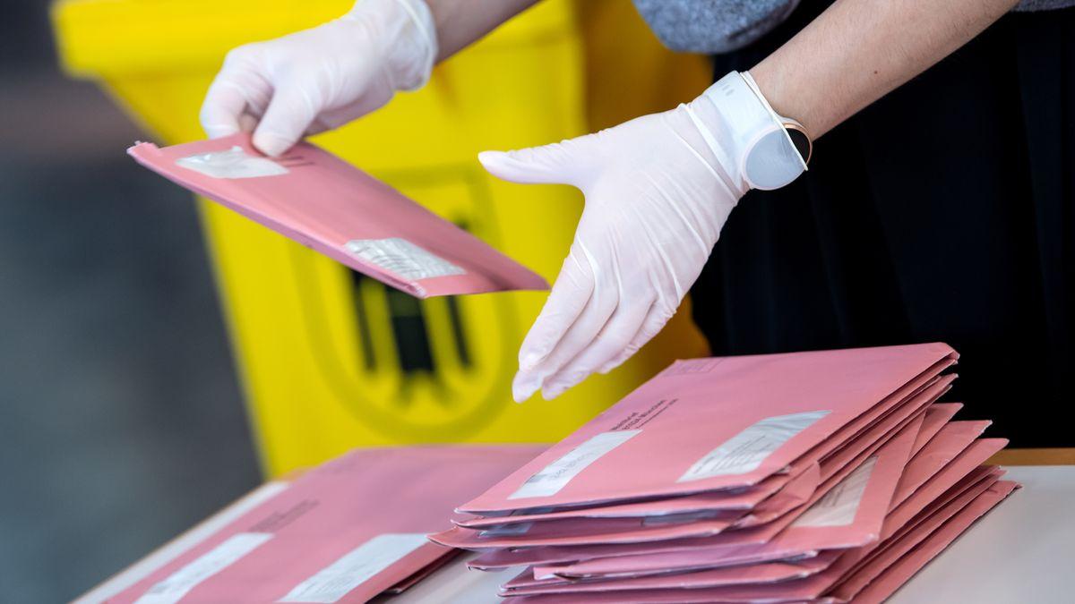 Wahlhelfer bereiten in einer Messehalle die Auszählung der Briefwahl vor