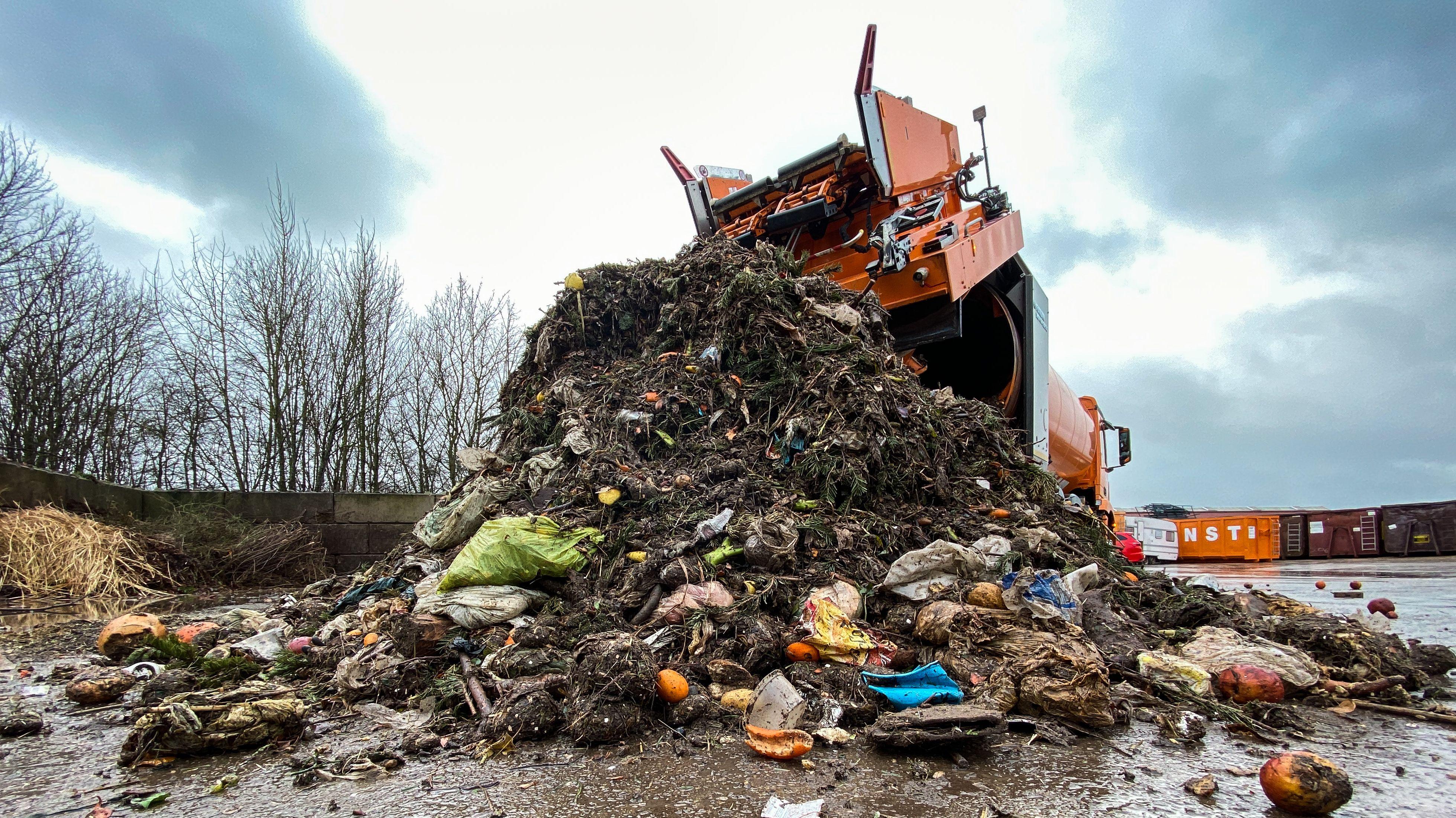 Mülllaster leert seine Bioabfall-Sammlung aus