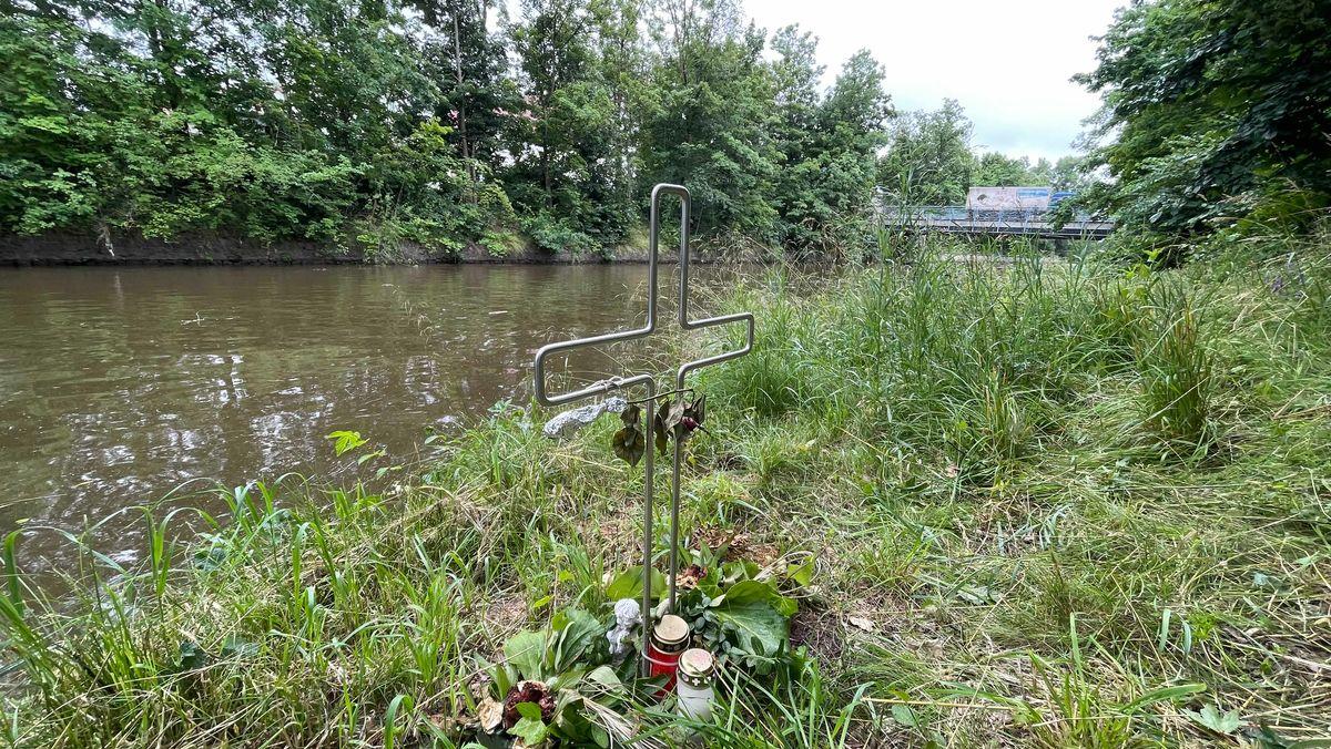 Ein Kreuz mit Blumen und Kerzen am Weidener Flutkanal.