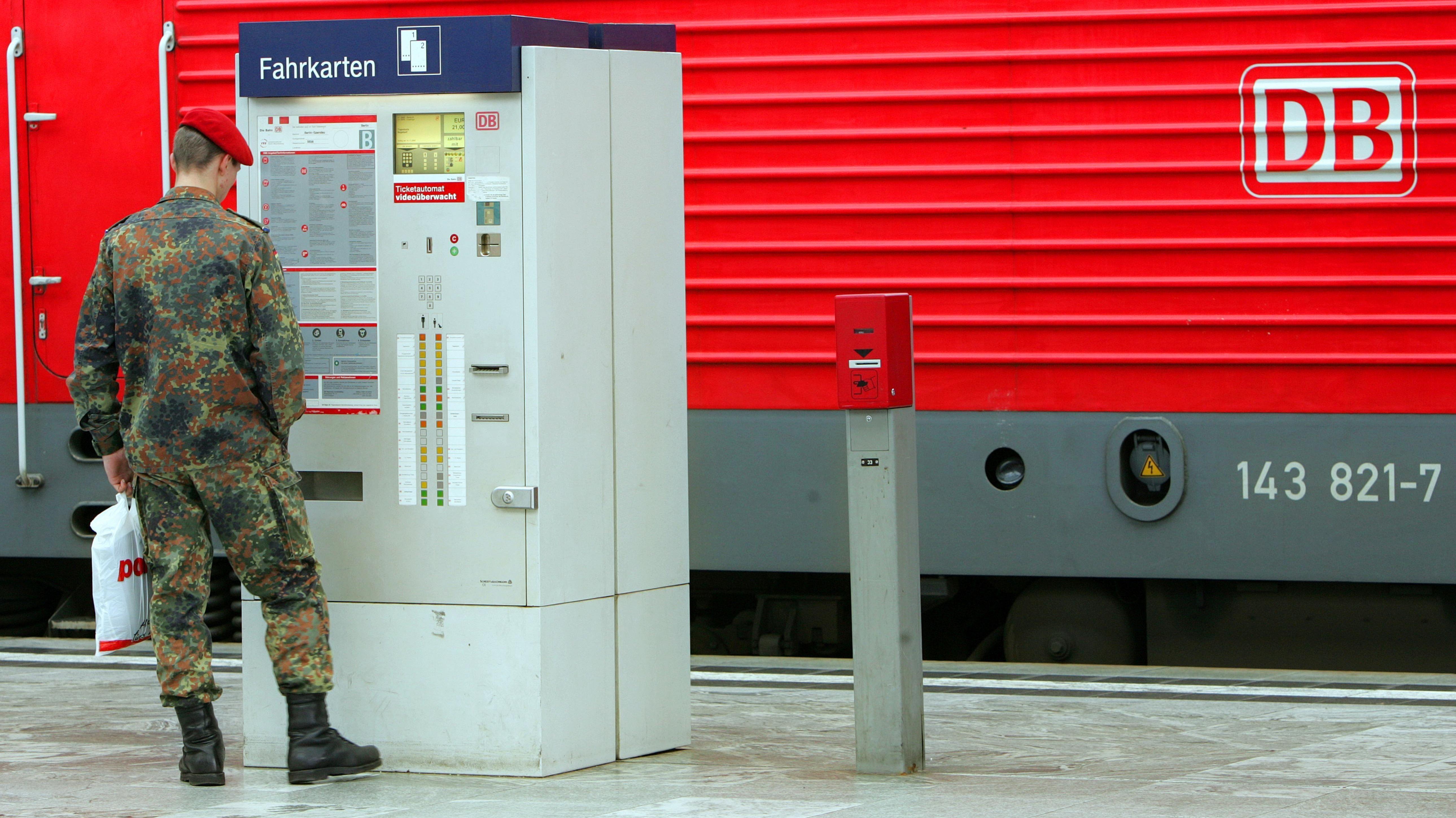Bundeswehrsoldat steht am Fahrkartenschalter der Deutschen Bahn.