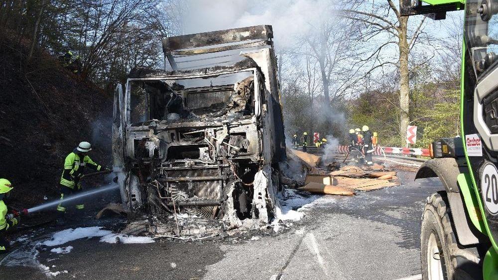 Die Feuerwehr löscht den völlig verkohlten Lkw auf der B388