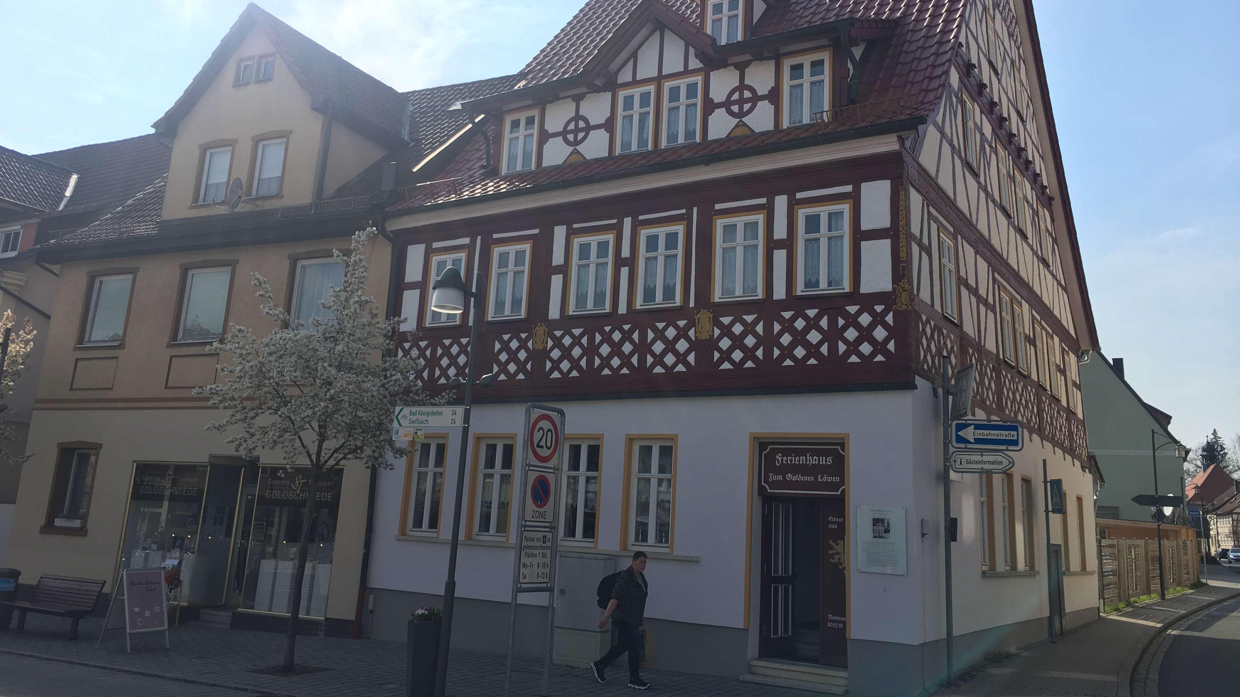Ein frisch saniertes Fachwerkhaus an einer Straßenecke zu der Fußgängerzone mit rot gestrichenen Balken und einem goldenen Schild über der Eingangstür