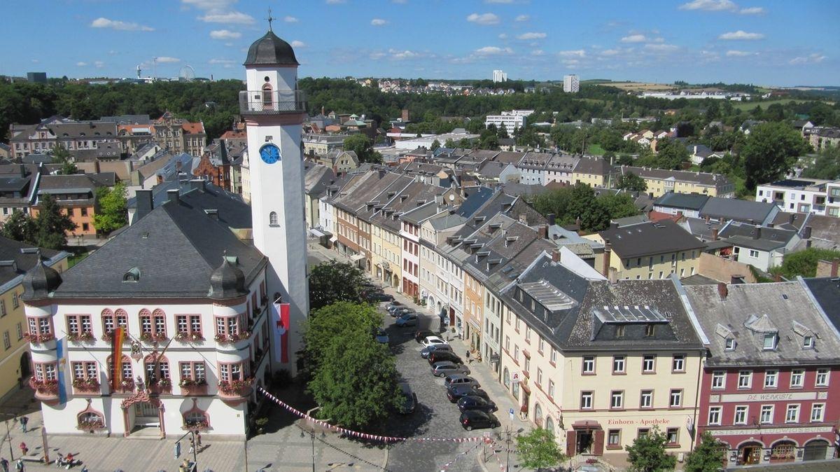 Das Rathaus von Hof, an dessen Fassade die Deutschland- und Bayernfahne hängen, aus der Vogelperspektive betrachtet, am Horizont blauer Himmel.