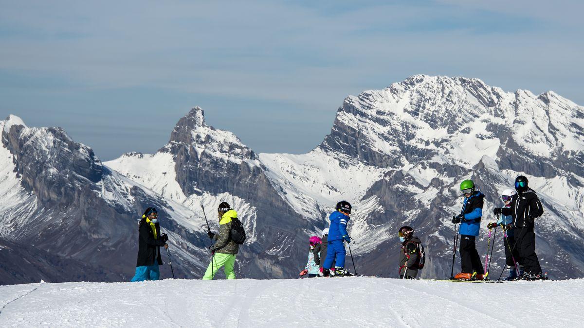 Skifahrer mit Gesichtsmasken fahren im Schweizer Skigebiets Verbier Ski.