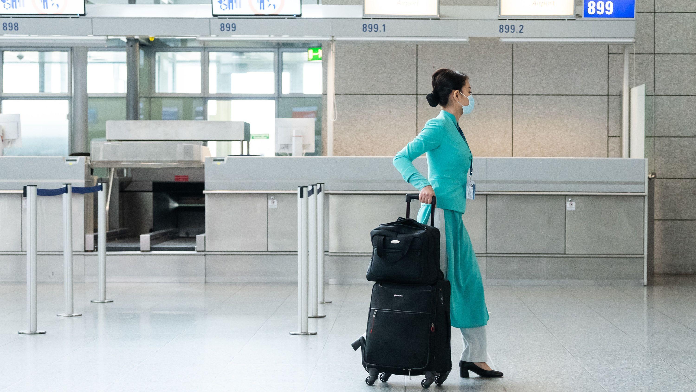 Flugbegleiterin mit Mundschutz am Flughafen Frankfurt