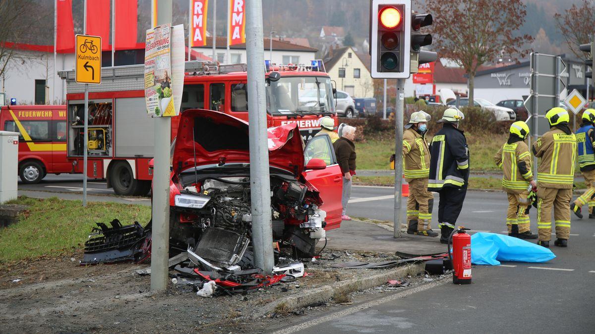 Einsatzkräfte der Feuerwehr stehen auf einer Kreuzung neben einem beschädigten Auto.
