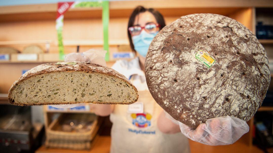 """Die Mitarbeiterin einer Bäckereifiliale der Kette Hofpfisterei hält einen angeschnitten Laib der Brotsorte """"Pfister Öko-Edame-Sonne"""" (l.) und einen Laib der Sorte """"Sonne"""" in den Händen."""