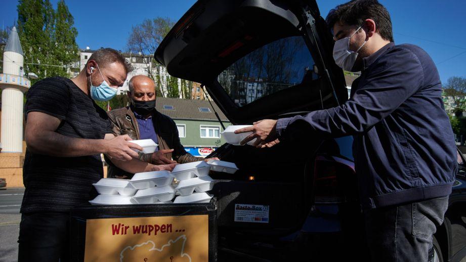 ARCHIV - 20.04.2020, Wuppertal: Muhammed Sönmez von der Ditib Zentralmoschee Wuppertal (r) belädt zusammen mit Helfern ein Auto mit Mahlzeitenpaketen.
