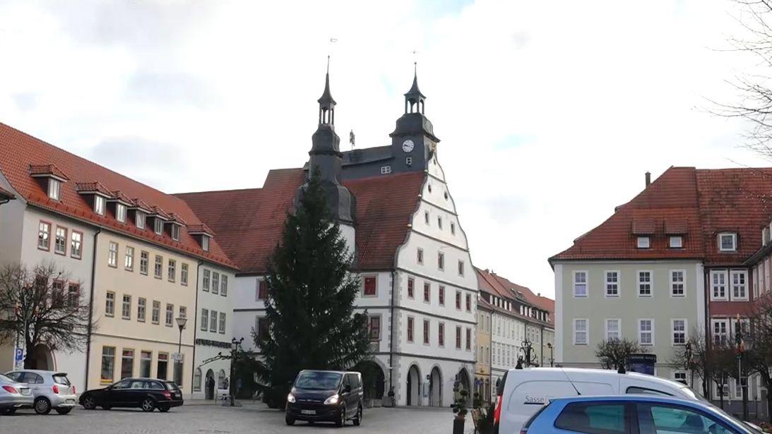 Vor dem historischen Rathaus von Hildburghausen steht ein Christbaum und parken Autos.