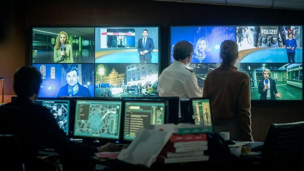 """Eine Szene aus dem Münchner """"Tatort"""": Polizei sieht dabei zu, wie Medien über die Angst vor einem zweiten Täter berichten."""