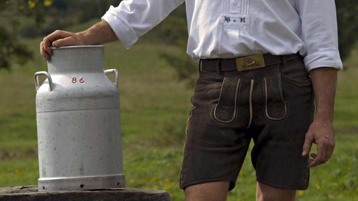 Ein Mann in Lederhose steht neben einer Milchkanne (Archivbild).