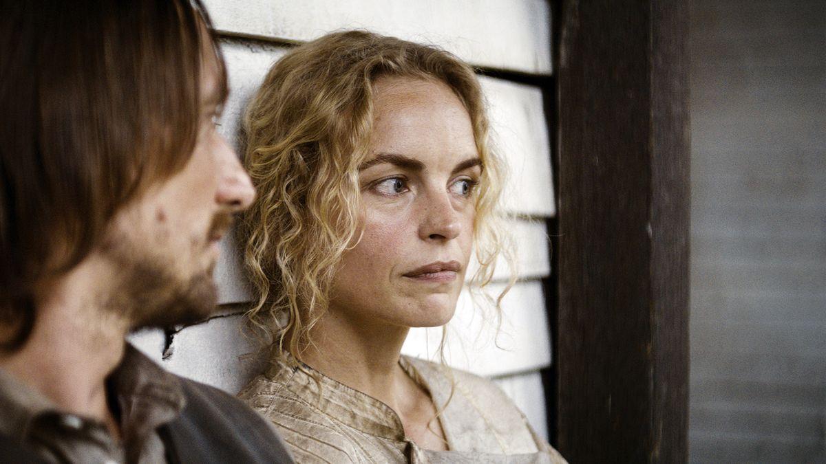 """Ein Mann und eine Frau lehnen an einer Häuserwand: Bild aus dem Film """"Gold"""""""