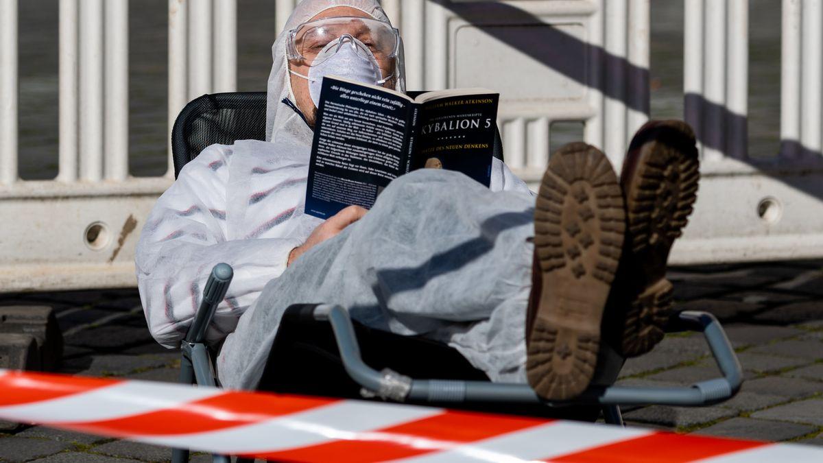 Mann in Schutzkleidung in Dresden liest ein Buch, 23.3.2020