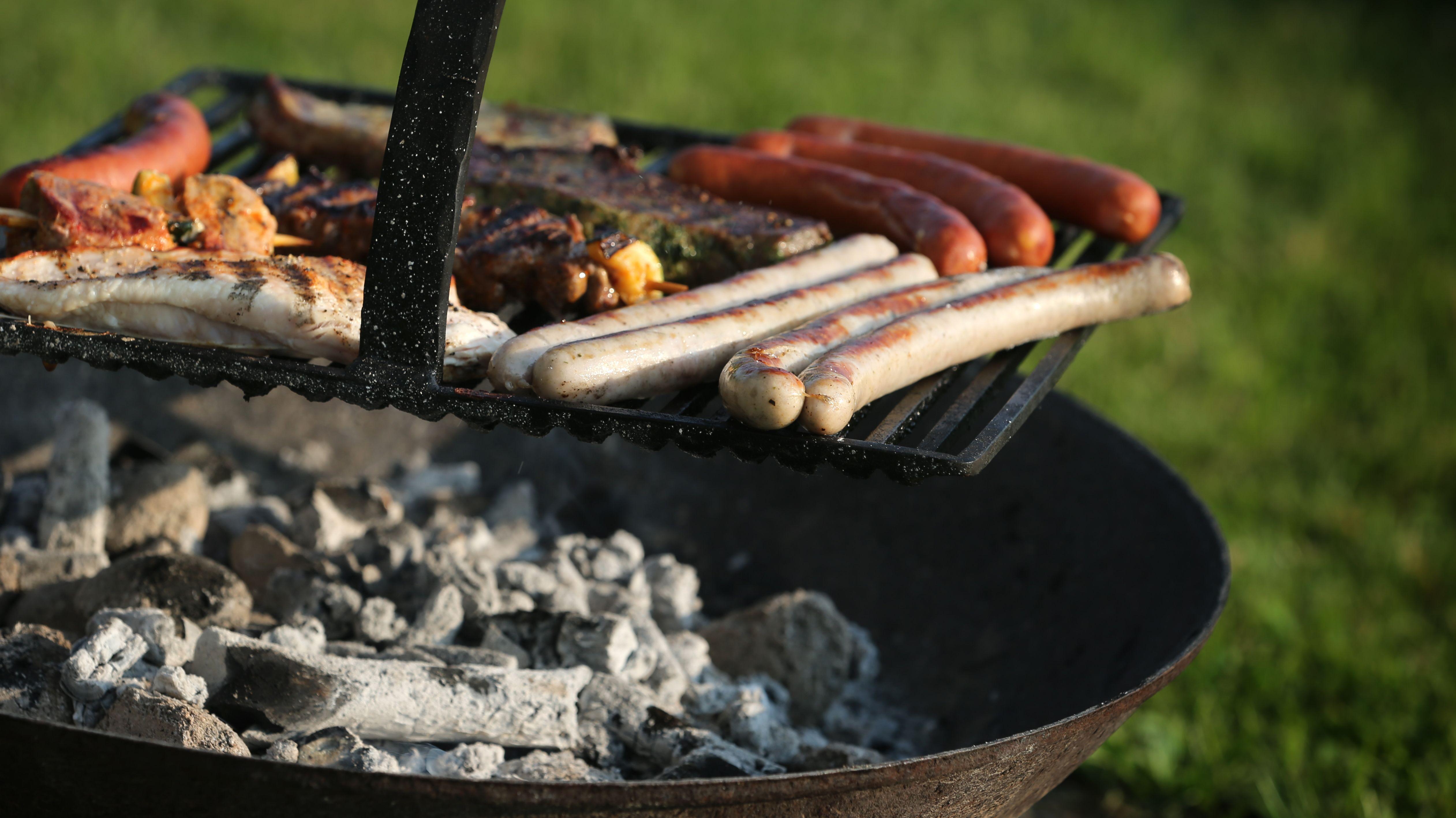 Würstl und Fleisch auf einem Kohle-Grill