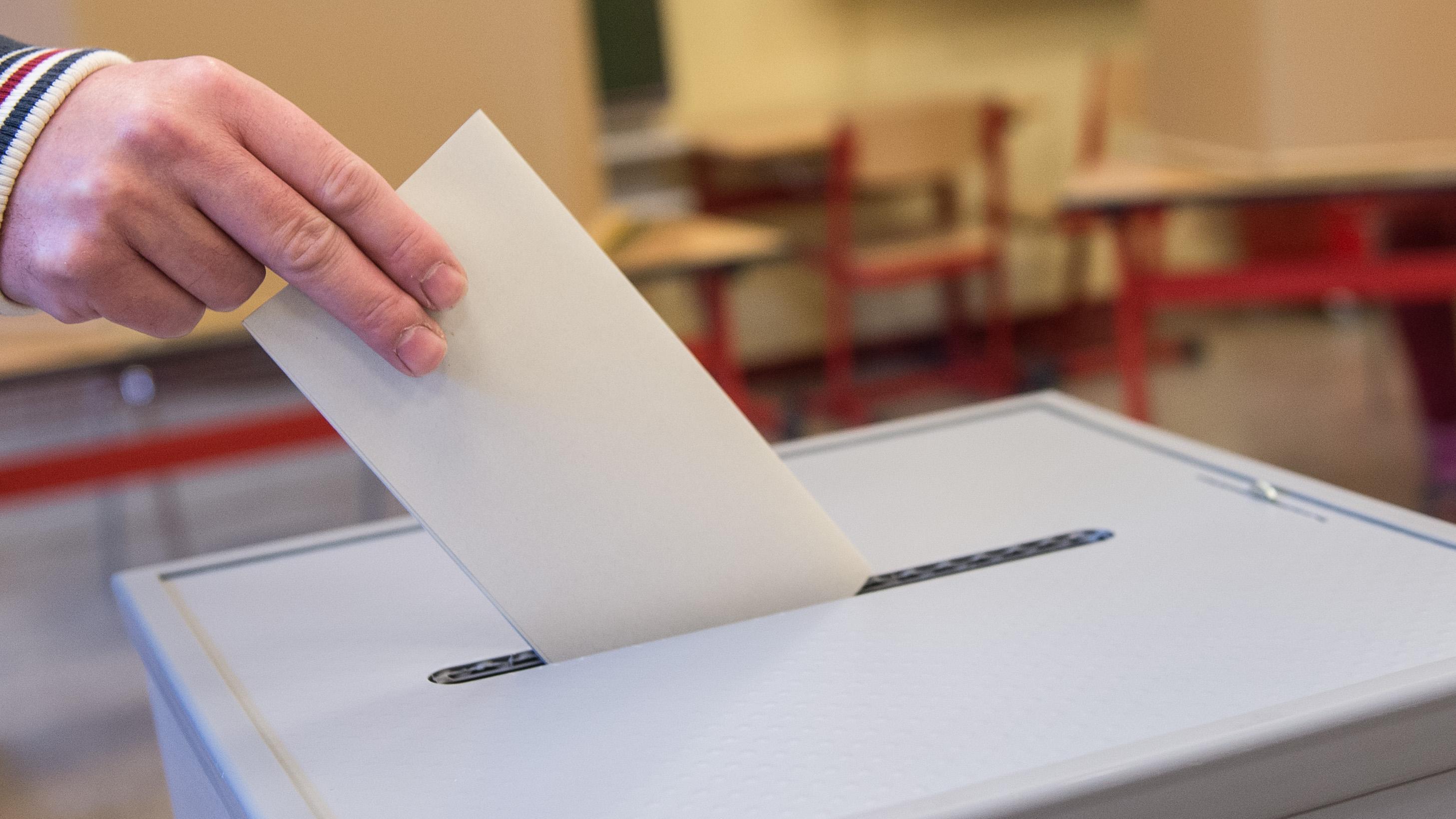 Stimmzettel wird in eine Wahlurne eingeworfen