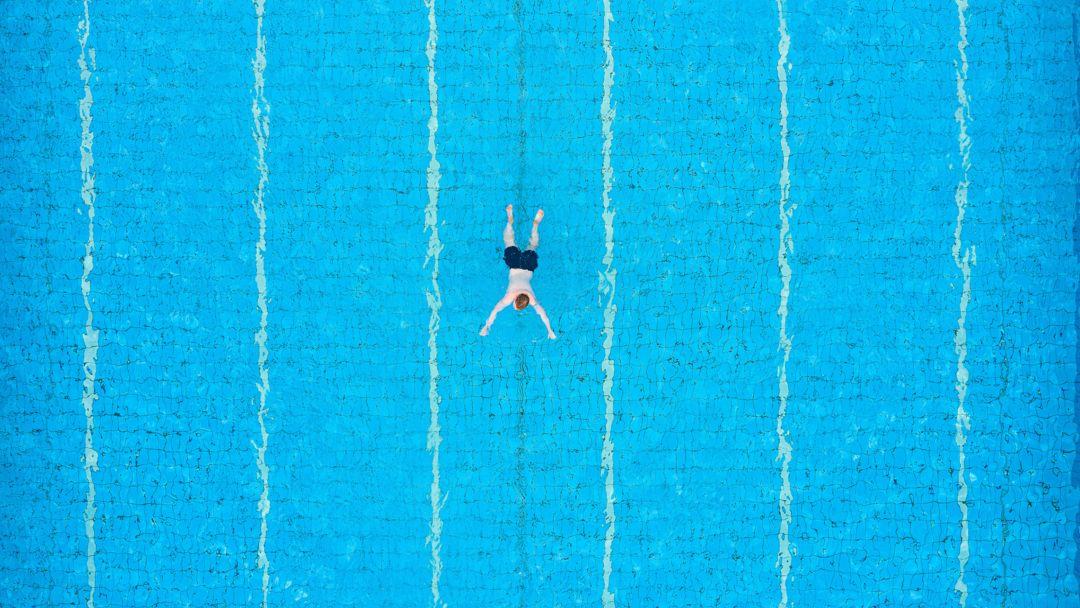 Ein Gast zieht in einem Freibad schwimmend seine Bahnen.