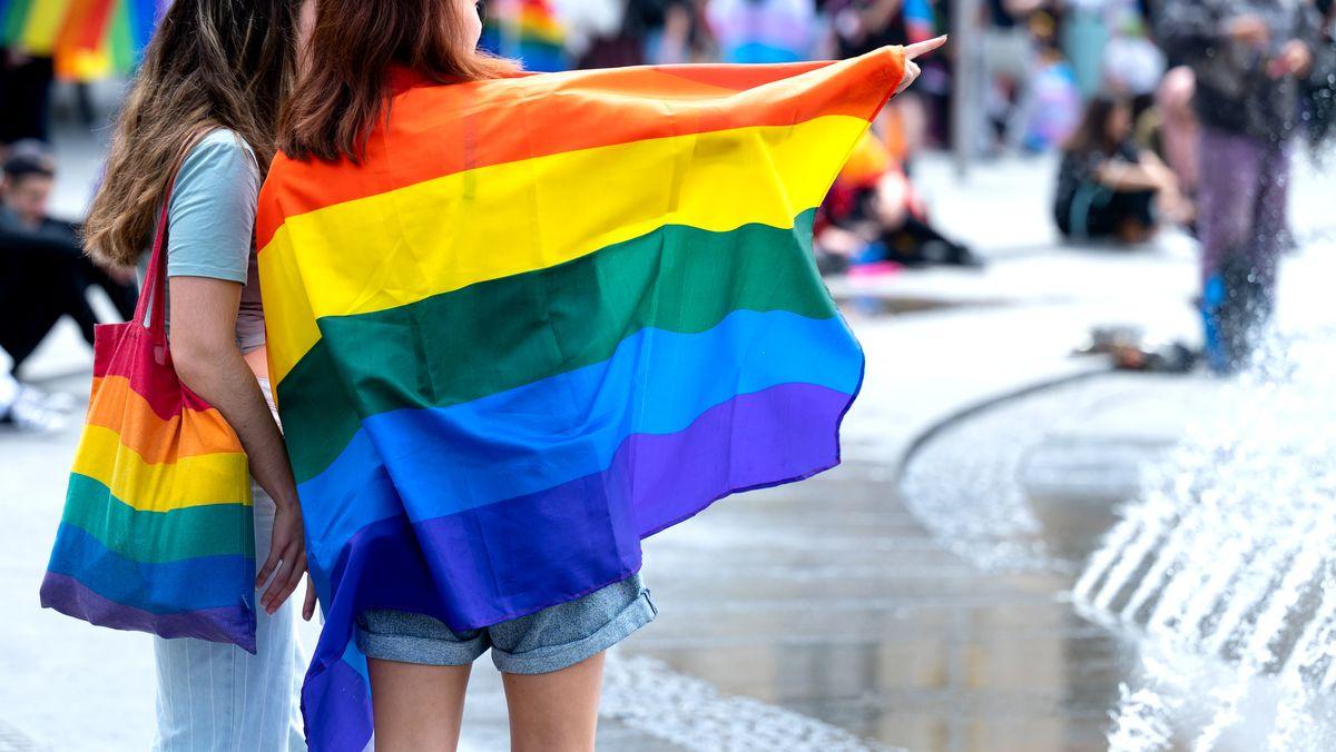 Teilnehmer eines CSD mit Regenbogenfahne