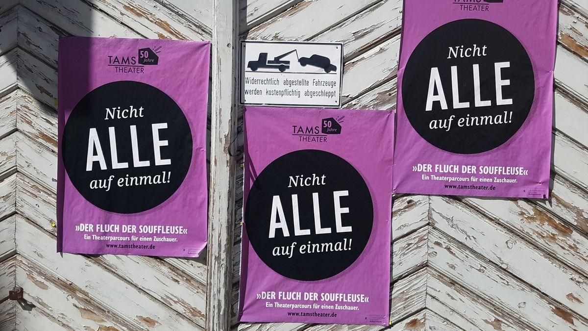 """Ein Garagentor mit Theaterplakaten des Münchner TAMS und dem Spruch """"Nicht alle auf einmal!"""""""
