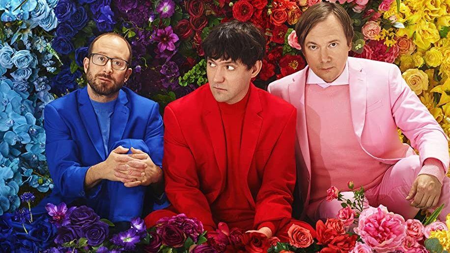 Mike Mogis, Conor Oberst & Nate Walcott (v.l.n.r.) in stark farbigen Outfits vor bunten Blumen