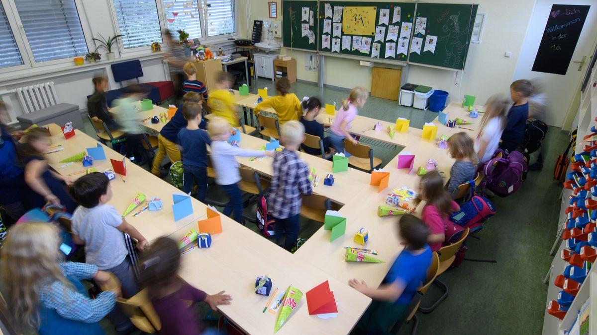 Grundschüler einer ersten Klasse in Dresden setzen sich am ersten Schultag auf die Plätze in ihrem Klassenzimmer.