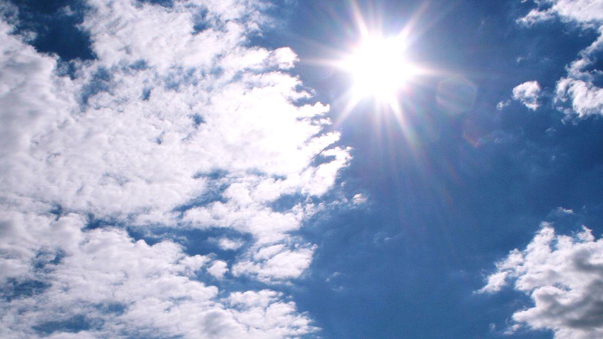 Sonne und Wolken am blauen Himmel