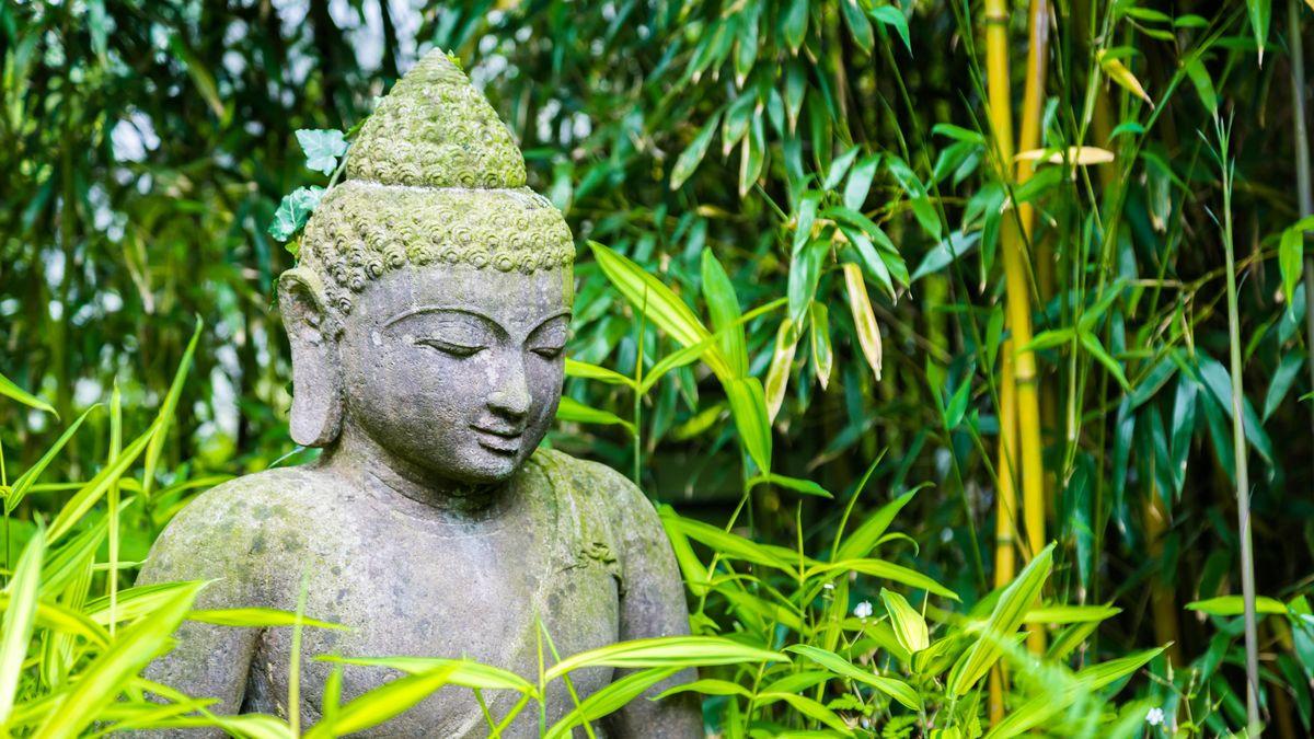Eine Buddha-Statue in einem Zen-Garten.
