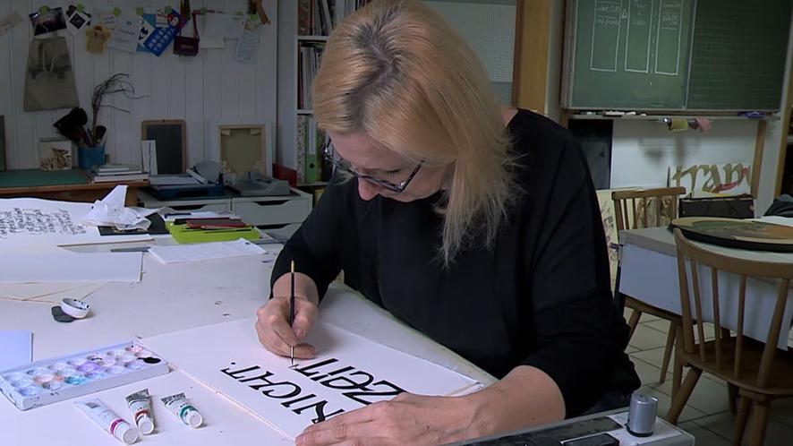 Andrea Wunderlich sitzt am Schreibtisch und zeichnet.